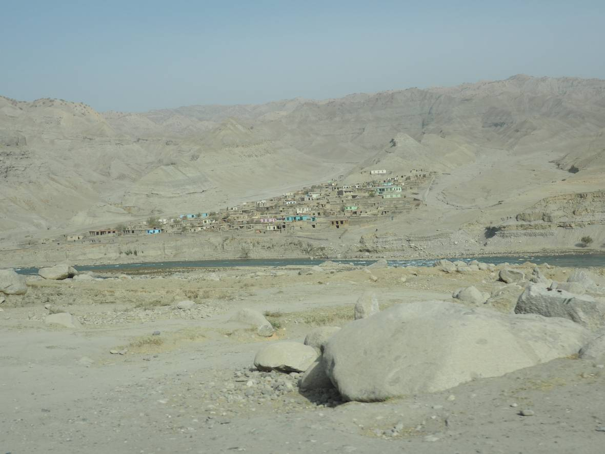 Afghanistan drought village against hillside - When disaster meets conflict