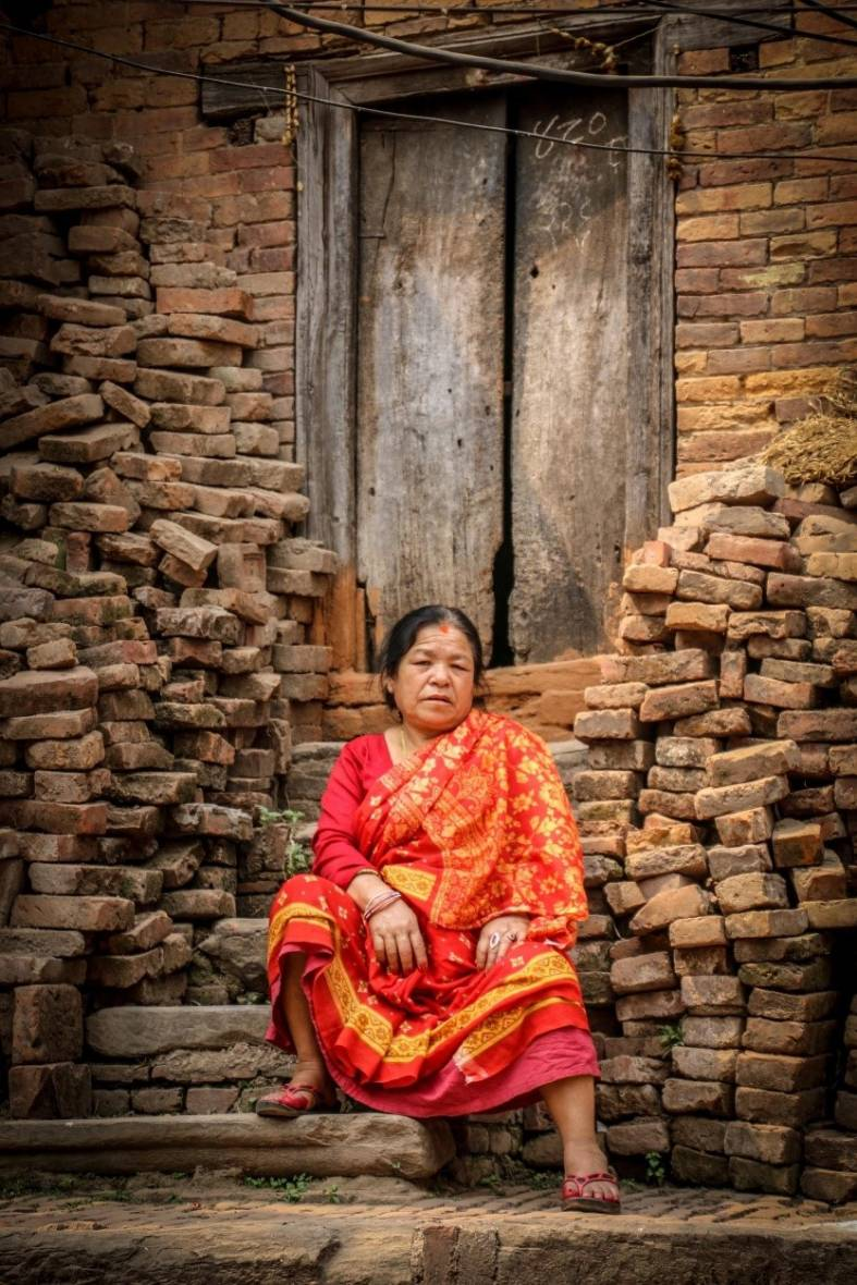 Woman sitting in front of a building under reconstruction in Bhaktapur, 2017, Nepal